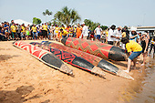 Brightly painted canoes with traditional tribal designs lie on the beach before the canoeing event at the International Indigenous Games in Brazil. 30th October 2015