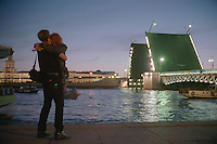 Saint Petersburg, Russia, June 2002..The mid-summer White Nights period when the sun sets only briefly is a time of festivals, entertainment and walks along the Neva River to watch the city bridges raise for shipping. Young lovers embrace as a ship passes through Palace Bridge at 2 am during the summer White Nights period..