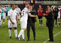 Alan Tate is hugged by former Swansea manager Brendan Rodgers and watched by former manager Roberto Martinez (L) and Brian Flynn (R) during the Swansea Legends v Manchester United Legends at The Liberty Stadium, Swansea, Wales, UK. Wednesday 09 August 2017