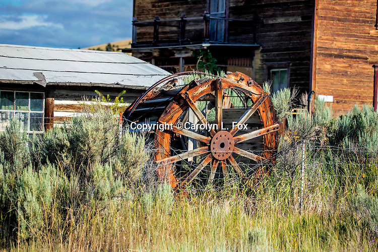 An old wheel leans against an old building.