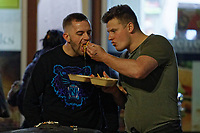 Pictured: Two men share a take-away meal in Swansea. Tuesday 31 December 2019 to Wednesday 01 January 2020<br /> Re: Revellers on a night out for New Year's Eve in Wind Street, Swansea, Wales, UK.