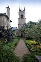 A gravel path, bordered by low topiary hedges, leads from Hackthorn Hall garden to the church of St Michael and All Angels