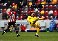 14th February 2021; Brentford Community Stadium, London, England; English Football League Championship Football, Brentford FC versus Barnsley; Toby Sibbick of Barnsley clears the ball away over Ivan Toney of Brentford.