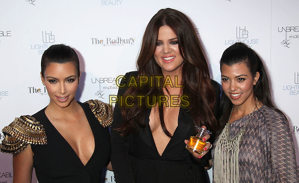 KIM KARDASHIAN. KHLOE KARDASHIAN ODOM & KOURTNEY KARDASHIAN .at the fragrance launch event for 'Unbreakable by Khloe and Lamar' perfume held at The Redbury Hotel, Hollywood, California, USA,.April 4th 2011..half length top cleavage black gold shoulder pads v-neck low cut epaulettes metal embellished sisters family siblings catsuit grey gray print dress kaftan brown zigzag one shoulder sleeve  plunging neckline  .CAP/ADM/MJ.©Michael Jade/AdMedia/Capital Pictures.