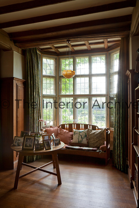 A cosy reading area under a mullion window overlooking the garden