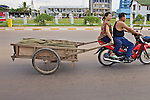 Man And Woman On Motorbike Pulling A Cart