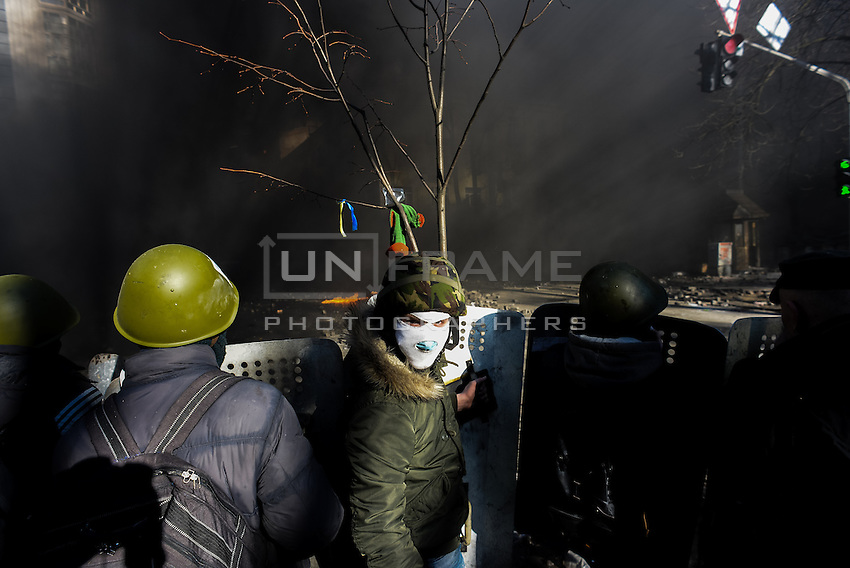 A hooded protester behind the first line of fire in Maidan square. Kiev, Ukraine