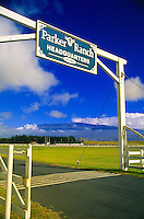 Entrance sign and road to Parker Ranch, a working cattle ranch and visitor attraction / museum in the community of Waimea or Kamuela, Big Island of Hawaii. In the background are science observatories on Mauna Kea, a dormant, often snow capped volcan