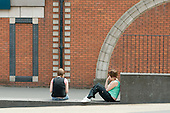 Bored teenagers sit on a wall in Walsall town centre, West Midlands