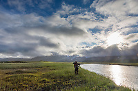 Photographer in the grassy meadow, Katmai National Park, Alaska Peninsula, southwest Alaska.