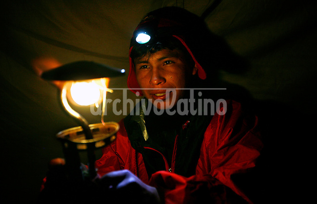 A porter adjusts the flame of a lamp in a tent near Cancha Cancha, Peru, in the Lares Valley, on May 15, 2008. The Lares Valley contains crystal-clear lakes and unspoiled mountain vistas. The Quechua, indigenous Inca people of Southern Peru with their small villages dotting the region, also populates the network of valleys.