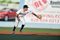 Asheville Tourists shortstop Jose Gomez (4) back hands the ball to the second baseman during a game against the Augusta GreenJackets at McCormick Field on July 16, 2017 in Asheville, North Carolina. The Tourists defeated the GreenJackets 12-3. (Tony Farlow/Four Seam Images)