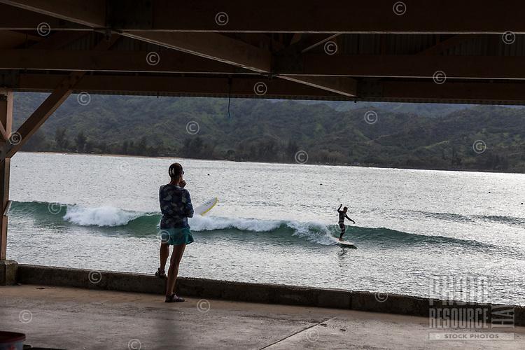 People on Hanalei Pier watch their friends surf in Hanalei Bay, Kaua'i.