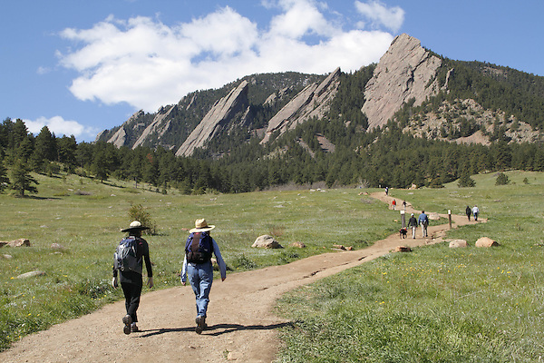 Women hikers at Chautauqua Park with the Flatirons rock formation behind, Boulder, Colorado, USA .  John leads private photo tours in Boulder and throughout Colorado. Year-round.