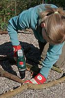 Kinder basteln Klangspiel aus Ästen, Mädchen bohrt mit Akkubohrer ein Loch in Ast