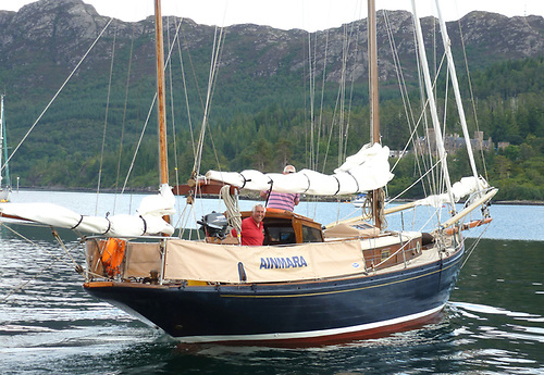 """Dickie Gomes with Ainmara during her Centenary Cruise of Scotland's West Coast in 2012. He'd bought her in 1967 despite being advised against """"getting involved with such an old boat"""", he owned her for more than fifty years, and she has since gone international under Swiss ownership, with her home port now at Dunkerque. Photo: W M Nixon"""