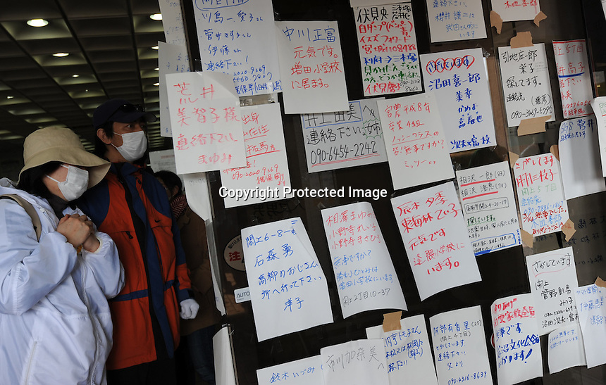 People look at evacuation lists and messages in the town of Natori, hoping to see the names of missing relatives.  The Tsunami devastated ahe entire pacifc coastline of Japan after the earthquake and tsunami devastated the area Sendai, Japan.<br /><br />photo by Richard Jones/ sinopix