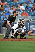 Home plate umpire Travis Eggert and Tulsa Drillers catcher Dustin Garneau (13) during a game against the Midland RockHounds on May 31, 2014 at ONEOK Field in Tulsa, Oklahoma.  Tulsa defeated Midland 5-3.  (Mike Janes/Four Seam Images)