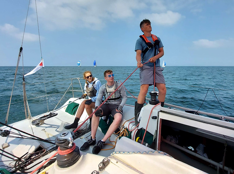Olivia Cure on the helm, David Carbery on the main, and Ronan Shepard trimming spinnaker on Tribal.