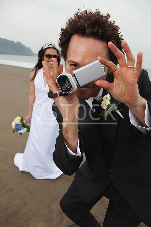 USA, California, San Francisco, Baker Beach, bride and groom with camcorder on beach