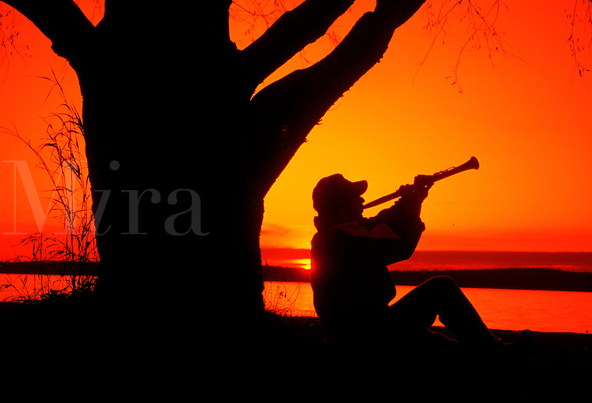 Silhouette of a man sitting beside a large tree, playing clarinet at sunset, by lakeshore