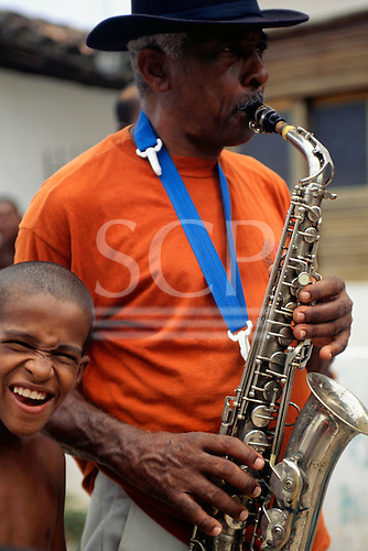 Itaparica Island, Bahia State, Brazil. Man playing a saxophone in a street procession.