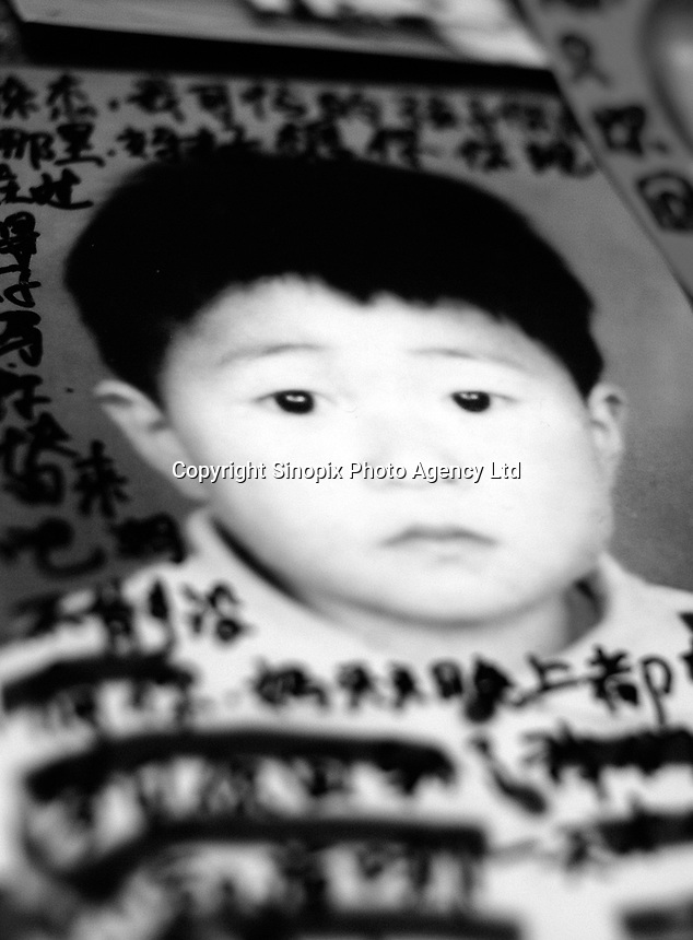 """Chen Zhijie, 5 years and 3 months, who was stolen, his mother believes by a neighborhood gang. Message read """"My poor son where are you? I miss you very much. Are you okay now? Please come back. Mum can't live without you. Mum dreams of you every night, dreaming that have come back to our sides. Don't know when can our dream comes true.""""..PHOTO BY SINOPIX"""