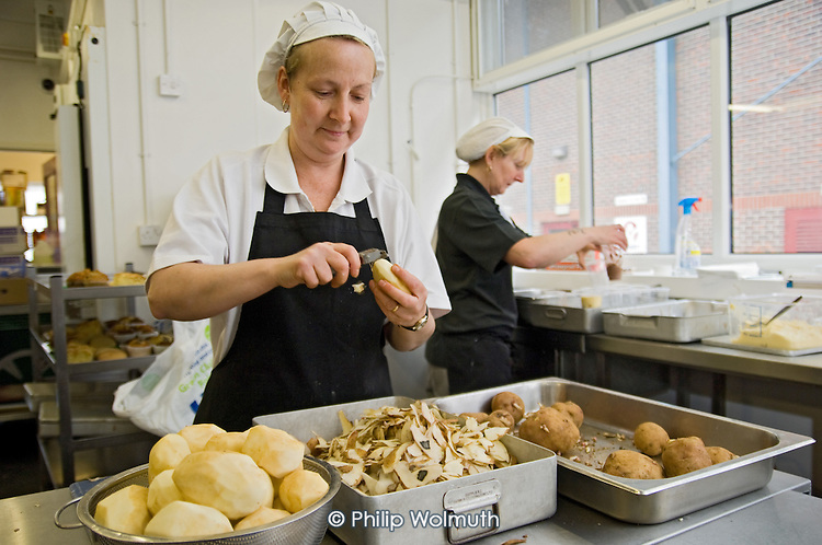 Catering staff peeling potatoes, Barking Abbey School, London