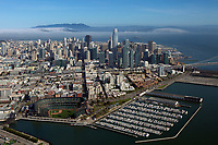 aerial photograph the San Francisco financial district skyline with the Giants Stadium and South Beach Marina in the foreground, San Francisco, California; fog moves through the Golden Gate