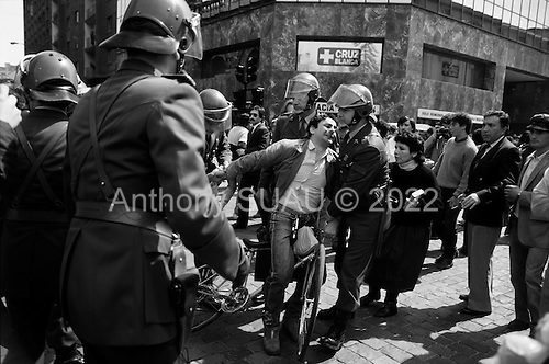 """Santiago, Chile.September 15, 1988..Chilean police arrest a man by pulling him off his bicycle when he shouted anti-General Augusto Pinochet slogans in support of the """"no"""" vote for the plebiscite. ..In 1988, General Augusto Pinochet ordered a plebiscite vote asking Chilean citizens whether he should continue in office. It produced a decisive """"no"""" vote and the following year he lost the first presidential election in 19 years. However, under a constitution crafted by his advisors, he remained as army commander until 1998. Pinochet continued to wield enormous power until his arrest in London on human rights charges in October 1998."""