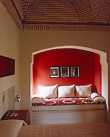 This bedroom has a niche where a comfortable daybed has been installed and is given dramatic effect with a bright red wall