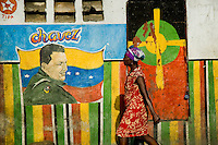 A Haitian woman walks down the street in front of the Hugo Chavez's painting in the La Saline market, Port-au-Prince, Haiti. Every day thousands of women from all over the city of Port-au-Prince try to resell supplies and food from questionable sources in the La Saline market. The informal sector significantly predominate within the poor Haitian economics and the regular shops virtually do not exist. La Saline is the largest street market area in Port-au-Prince.
