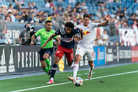 FOXBOROUGH, MA - JUNE 23: Tajon Buchanan #17 of New England Revolution dribbles down the wing as Sean Nealis #15 of New York Red Bulls defends during a game between New York Red Bulls and New England Revolution at Gillette Stadium on June 23, 2021 in Foxborough, Massachusetts.