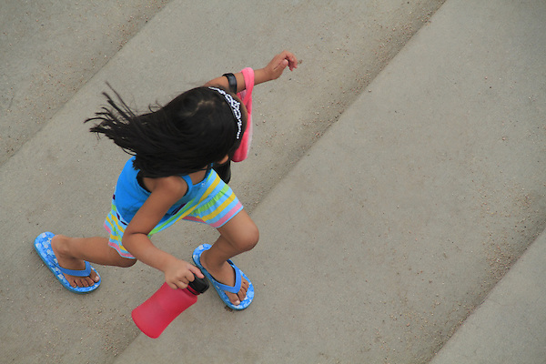 Young Hispanic girl running upstairs in Denver, Colorado. .  John offers private photo tours in Denver, Boulder and throughout Colorado. Year-round Colorado photo tours.