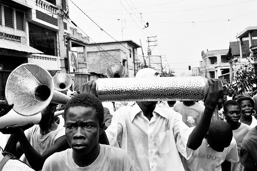 Haitian men playing home-made horns and drums during a pro-Preval demonstration in Bel Air on the day of the elections in Port-Au-Prince.