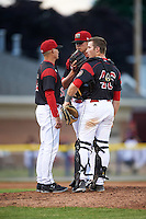 Batavia Muckdogs pitching coach Chad Rhoades (15) talks with pitcher Trenton Hill (39) and catcher David Gauntt (46) during a game against the West Virginia Black Bears on June 28, 2016 at Dwyer Stadium in Batavia, New York.  Batavia defeated West Virginia 3-1.  (Mike Janes/Four Seam Images)