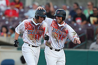 Cal Towey #13 of the Inland Empire 66ers is greeted by teammate Dennis Raben #28 after hitting a home run while wearing Zombie Apocalypse Night jersey's against the Visalia Rawhide at San Manuel Stadium on June 12, 2014 in San Bernardino, California. Inland Empire defeated Visalia, 4-2. (Larry Goren/Four Seam Images)