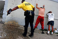 Sgt. Kervin Beasley of the Des Moines Police Department empties a bottle of beer while placing two men under arrest for public intoxication near 6th Avenue and University Avenue in Des Moines.