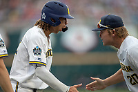 Michigan Wolverines outfielder Jordan Brewer (22) celebrates with teammate Willie Weiss (20) after scoring a run during Game 1 of the NCAA College World Series against the Texas Tech Red Raiders on June 15, 2019 at TD Ameritrade Park in Omaha, Nebraska. Michigan defeated Texas Tech 5-3. (Andrew Woolley/Four Seam Images)
