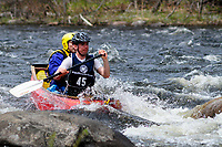 Two canoeists paddling an open canoe on the Hudson River in the Hudson White Water Derby, Adirondack Forest Preserve, New York