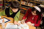 Elementary school Grade 5 male and female students working together on geography social studies assignment working with map book horizontal