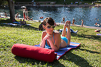 Beautiful woman sunbathes at Barton Springs Pool with swimmers in the spring pool swimming, Austin, Texas