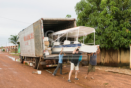 """Canarana, Mato Grosso, Brazil. Taking the boat """"Coração do Brasil"""" out of the delivery truck."""