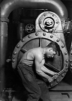 "Records of the Work Progress Administration. <br /> Lewis Hine's 1920 Power house mechanic working on steam pump, one of his ""work portraits"", shows a working class American in an industrial setting. The carefully posed subject, a young man with wrench in hand, is hunched over, surrounded by the machinery that defines his job. But while constrained by the machinery (almost a metal womb), the man is straining against it—muscles taut, with a determined look—in an iconic representation of masculinity."