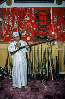 Nizwa, Oman.  Souvenir Shop.  Shopper Examining an old Gun.