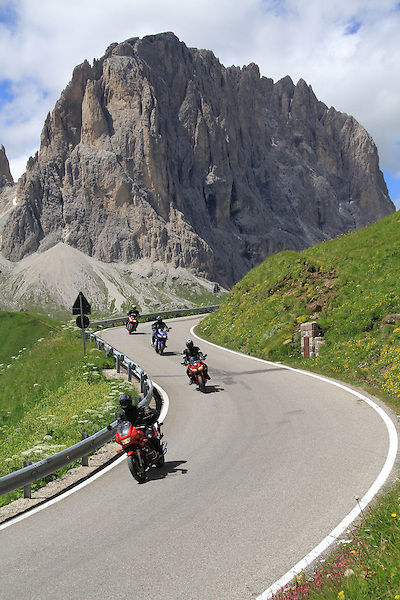 Motocyclists in the Dolomites, Sassolunga behind, northern Italy, Europe. .  John offers private photo tours in Denver, Boulder and throughout Colorado, USA.  Year-round. .  John offers private photo tours in Denver, Boulder and throughout Colorado. Year-round.