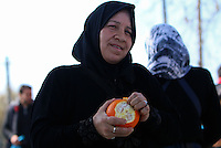 Pictured: A woman opens an orange given by one of the farmers at the road block Tuesday 23 February 2016<br /> Re: Migrants on their way back to Athens have been caught by the blocked off motorway at Tembi, where local farmers have closed off the road, protesting against pension and welfare reforms near Trikala, Greece.