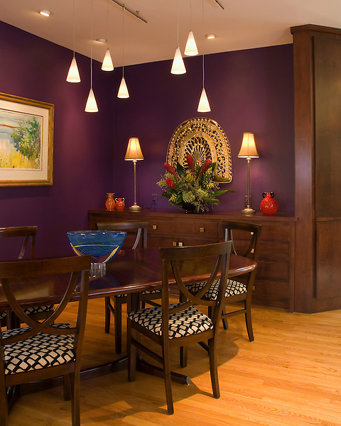 Purple walls, pendant lights, rich brown wood table and cabinet set on a light colored oak floor in a Richmond dining room
