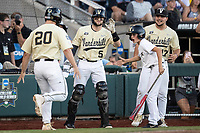 Vanderbilt Commodores designated hitter Ty Duvall (20) is greeted by his teammates after scoring against the Michigan Wolverines during Game 3 of the NCAA College World Series Finals on June 26, 2019 at TD Ameritrade Park in Omaha, Nebraska. Vanderbilt defeated Michigan 8-2 to win the National Championship. (Andrew Woolley/Four Seam Images)