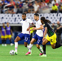 DALLAS, TX - JULY 25: Kellyn Acosta #23 and Sebastian LLetget #17 of the United States bring the ball up the field in front of Daniel Johnson #16 of Jamaica during a game between Jamaica and USMNT at AT&T Stadium on July 25, 2021 in Dallas, Texas.
